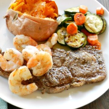 grilled steak, shrimp and vegetables on a large white plate with a baked sweet potato