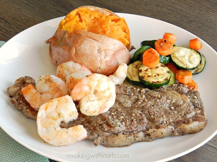Grilled steak and Shrimp with a side of grilled vegetables and a sweet potato on a white plate