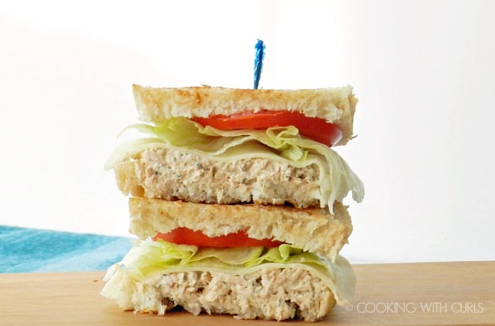 A Tuna on Grilled Sourdough topped with provolone cheese,lettuce and tomato, but in half and stacked on a wood board.