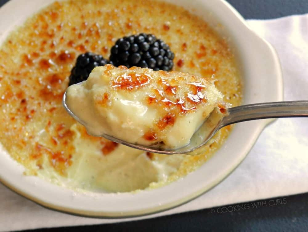 A big spoonful of Creme Brulee hovering over the dessert in a ramekin topped with two blackberries.