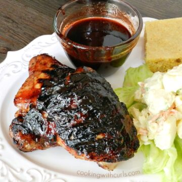 barbecue chicken, potato salad, cornbread and a bowl of barbecue sauce on a white plate with a bottle of sauce in the background