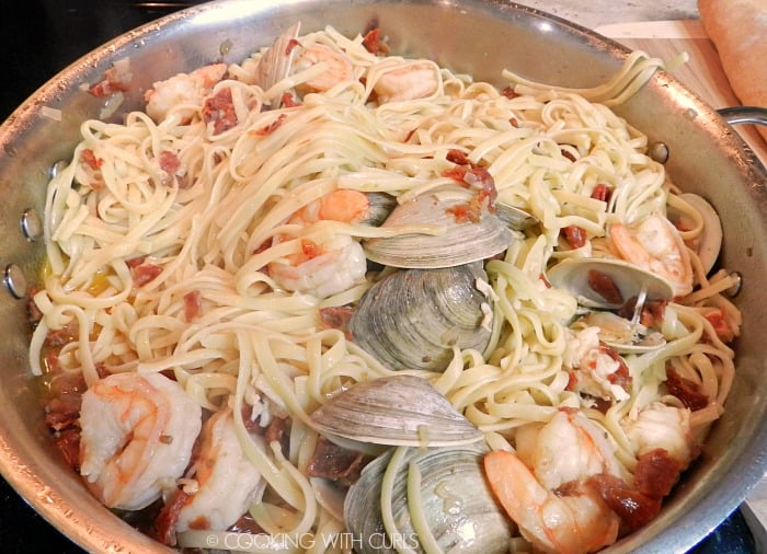 Cooked pasta noodles stirred into the frying pan with the seafood, tomatoes, garlic and shallots.