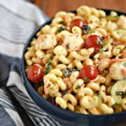 Spiral pasta, mozzarella cheese, cherry tomatoes, zucchini and black olives mixed together in a blue bowl.