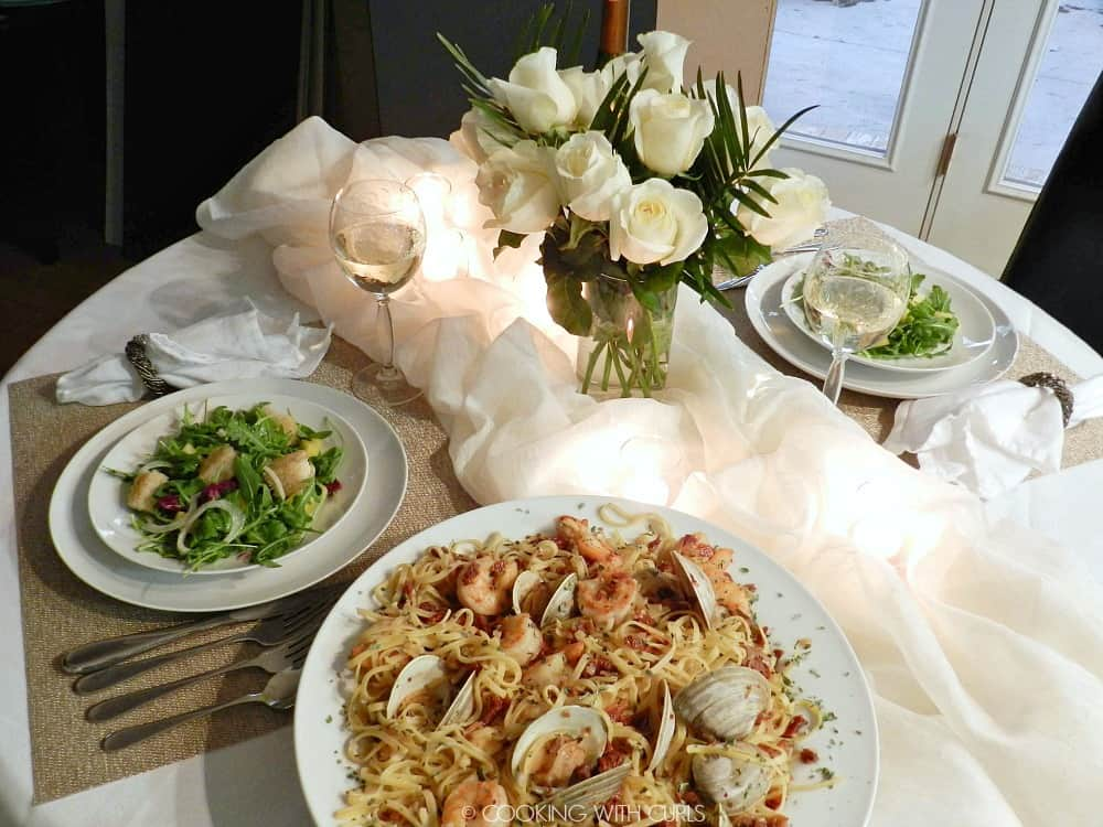 Romantic dinner table set with white roses, tealight candles in billowy white fabric, two glasses of white wine, two shaved fennel salads and a large bowl of Italian seafood pasta.