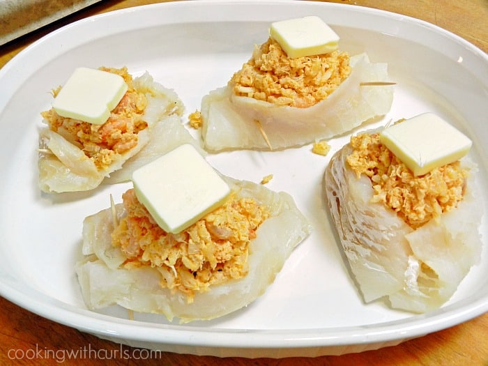 Shrimp and Crab Stuffed Cod topped with butter in a white baking dish