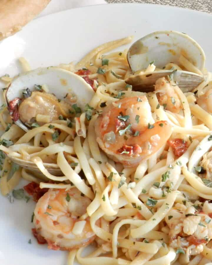 A large white plate with shrimp, clams and noodles in a garlic sauce.