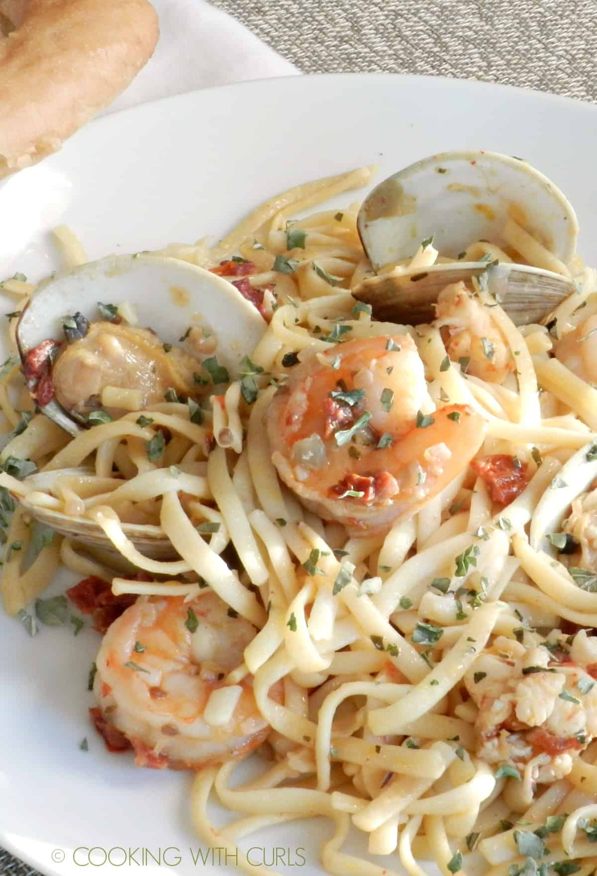 a close up view of a plate of Italian Seafood Pasta on a white plate.