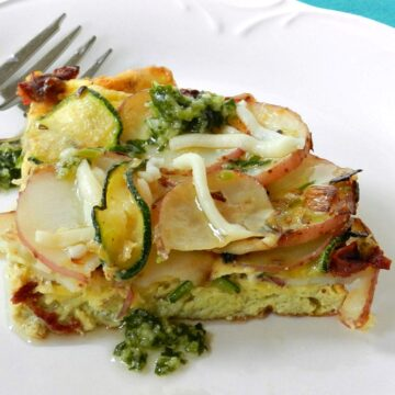 layers of Italian Frittata sliced into a wedge and served on a white plate