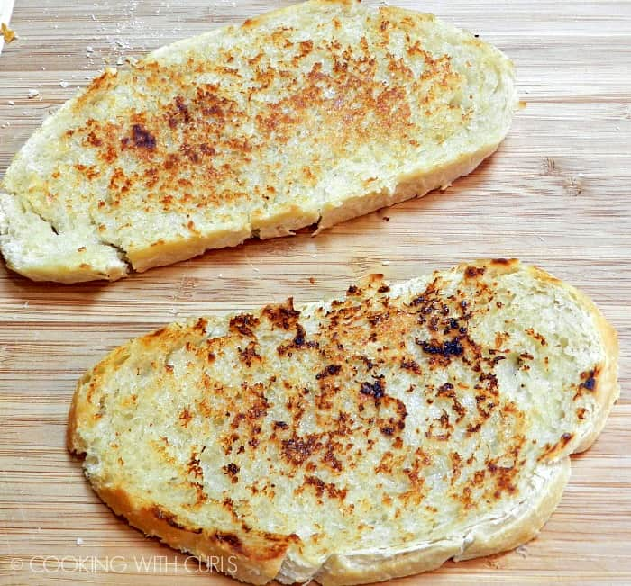 Two slices of grilled sourdough bread laying on a wood cutting board.