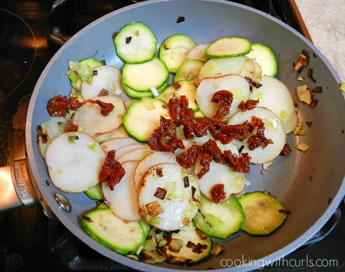 tomatoes sliced potato and sliced zucchini in a small non-stick pan