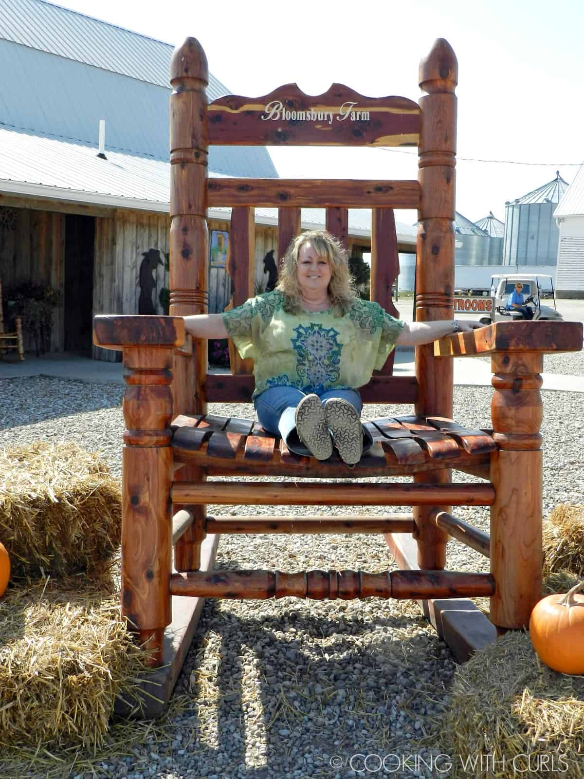 a woman with curly blonde hair sitting in a giant wood chair on a pumpkin patch.