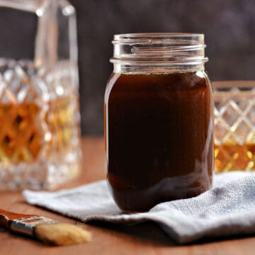 Whiskey glaze in a glass jar with a bottle and glass of whiskey in the background.