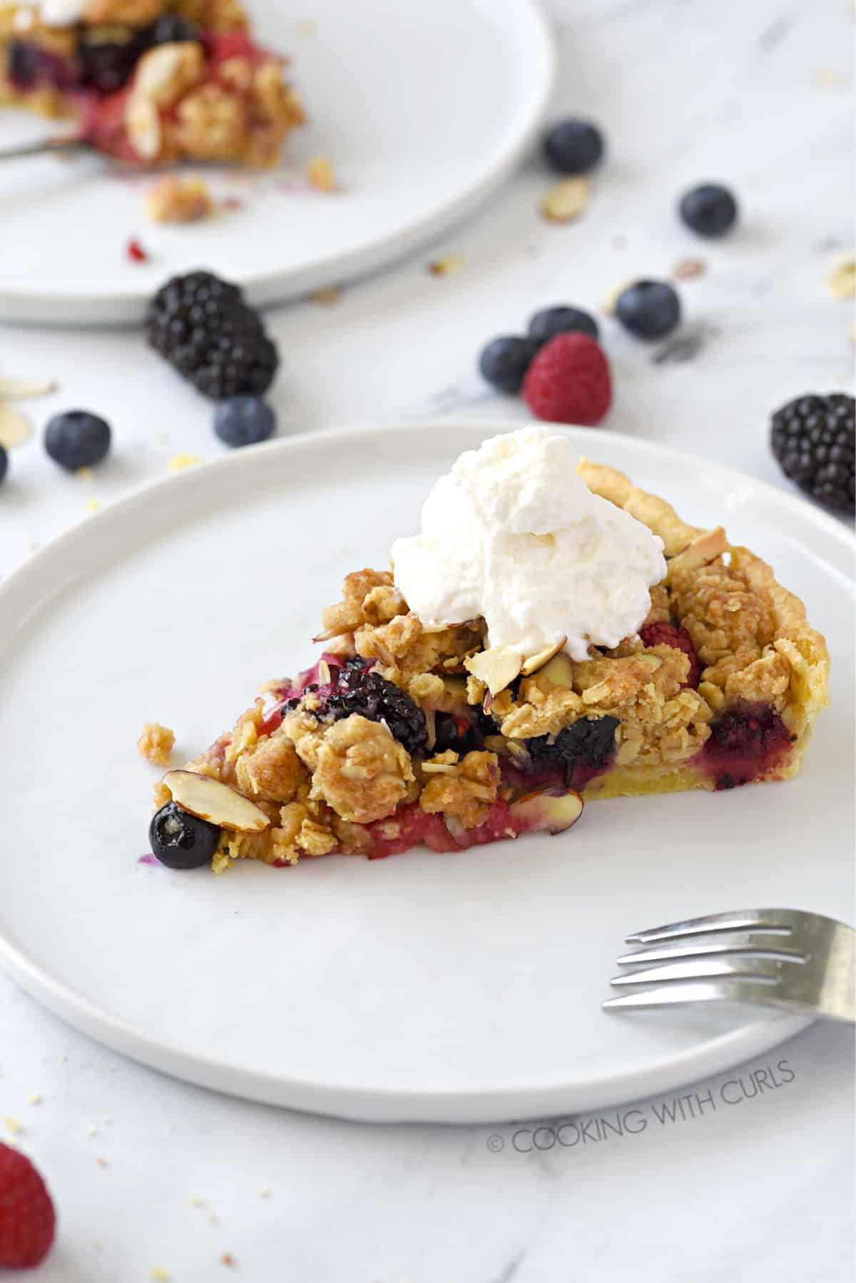 a slice of apple-berry crumble topped with irish whiskey whipped cream sitting on a white plate with a fork laying on the edge and mixed berries laying behind.