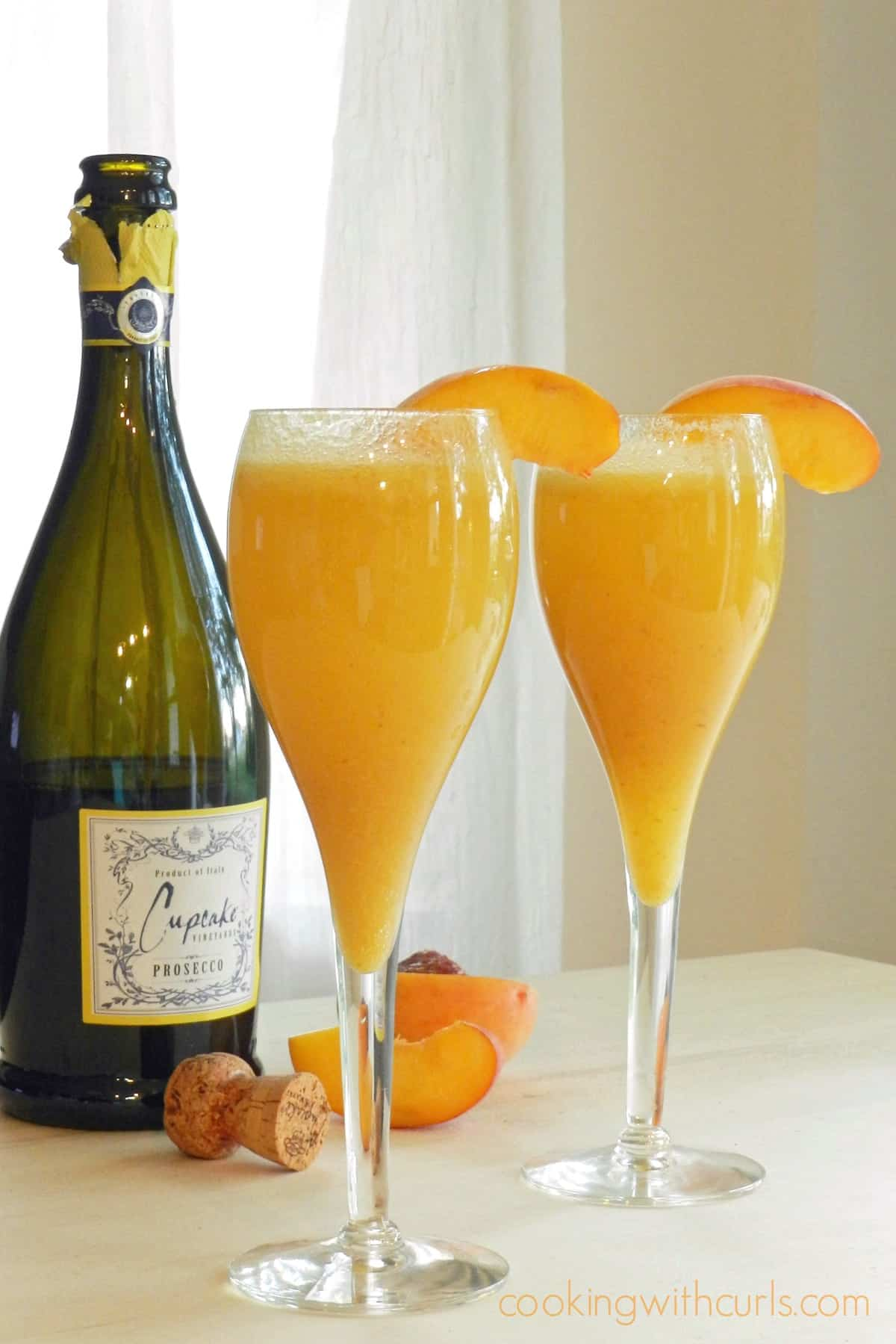 Two champagne glasses filled with Peach Bellini with a bottle of prosecco in the background.