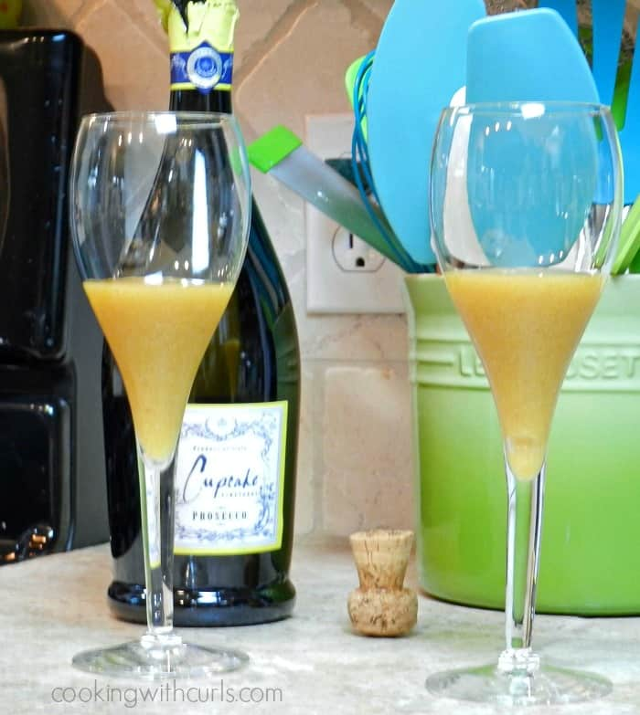 Two champagne glasses filled half way with pureed peaches and a bottle of Prosecco in the background.
