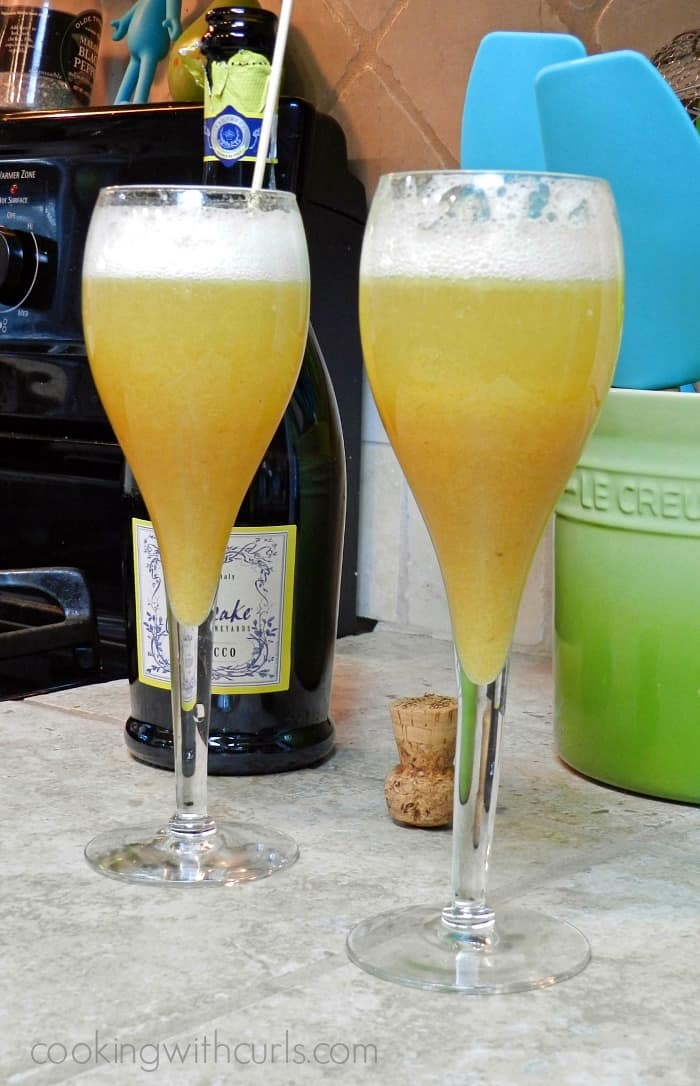 two champagne glasses filled with pureed peaches and prosecco with the bottle in the background.