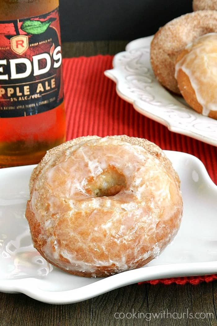apple ale doughnuts sitting on white plate with a bottle of apple ale in the background