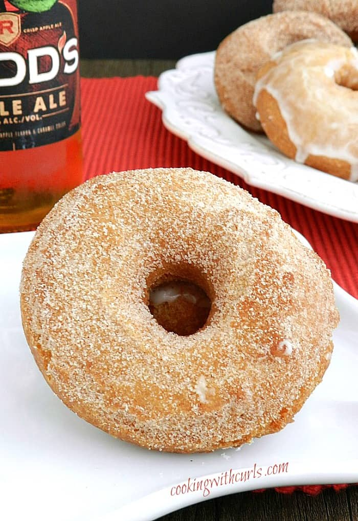 cinnamon sugar coated doughnut on a white plate with a bottle of apple ale in the background