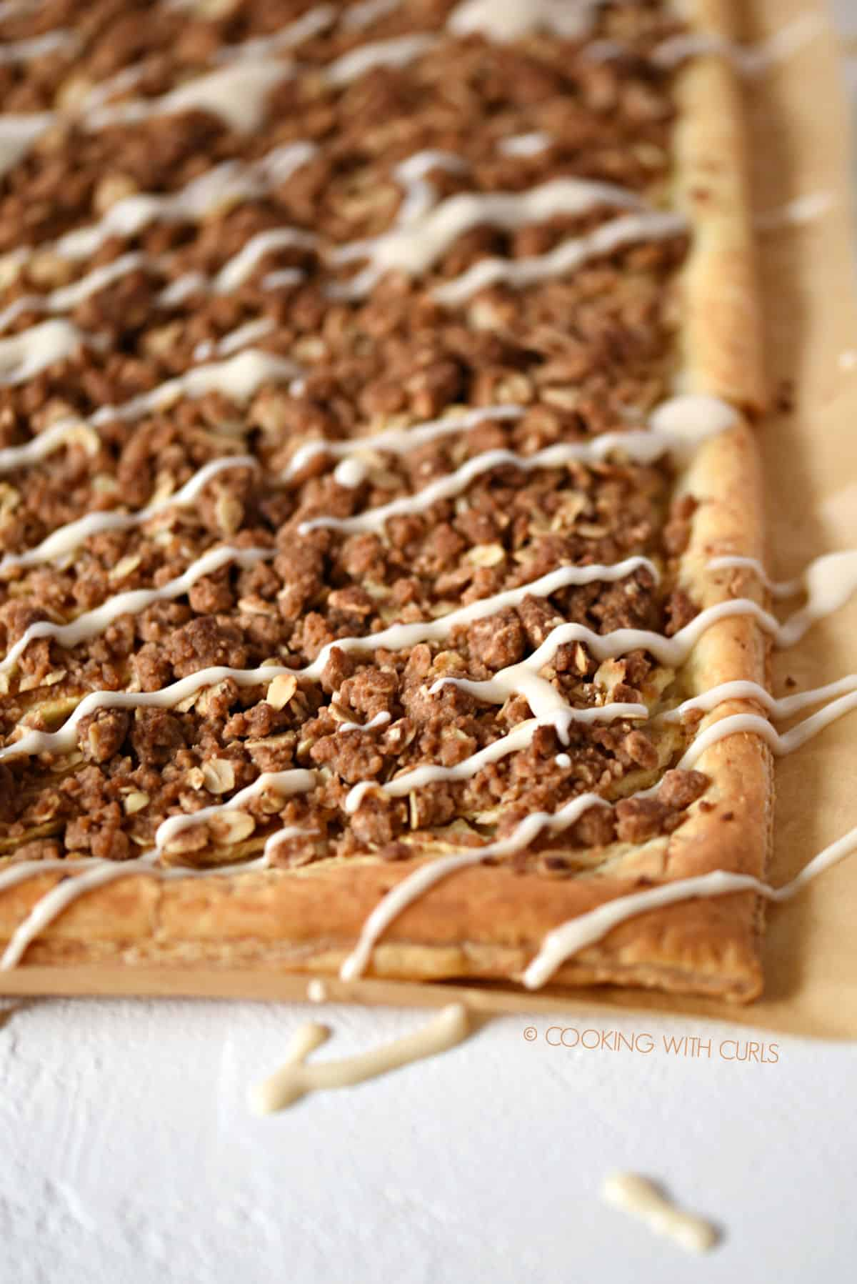 Apple Streusel Pizza with crumble topping over sliced apples and a glaze drizzle.