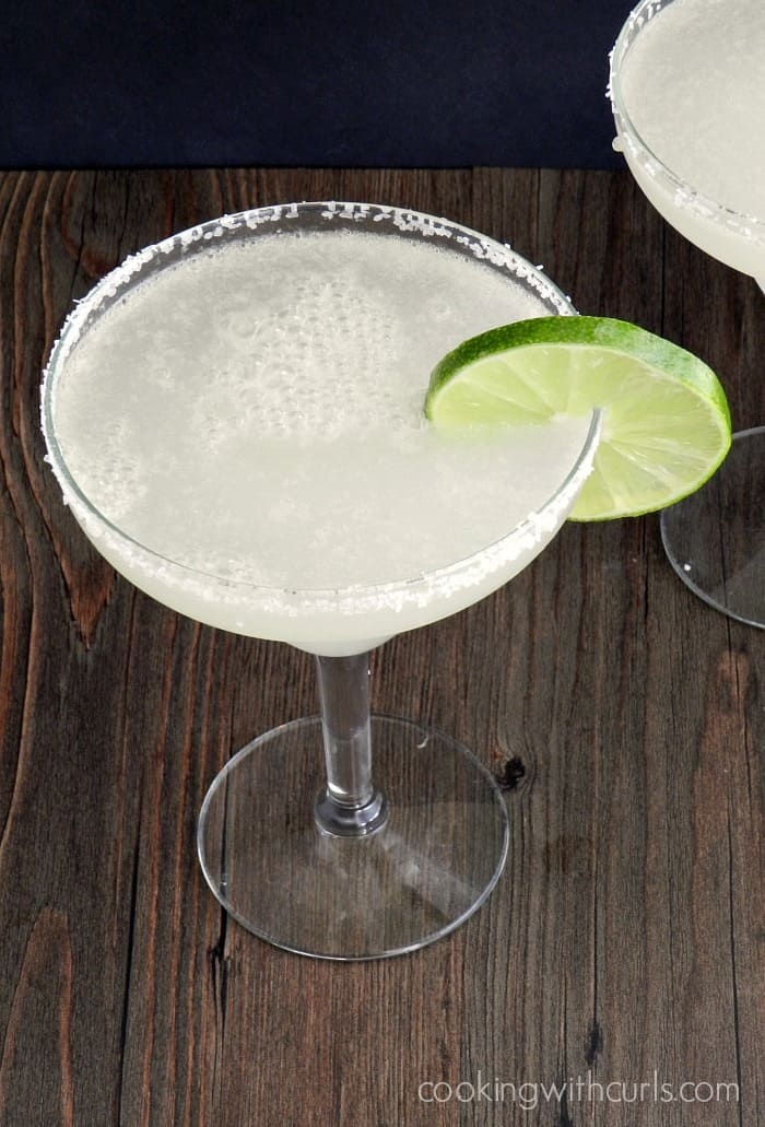 margarita in a margarita glass with a salted rim and lime slice