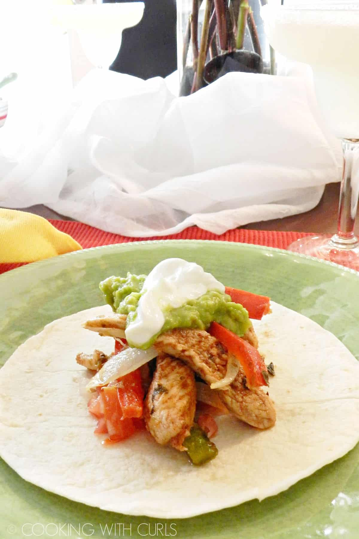 Strips of chicken, onion, and peppers stacked on a flour tortilla, topped with guacamole and sour cream.