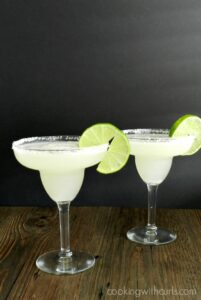 Fresh made Margaritas in margarita glasses with a salted rim and a lime slice on the edge