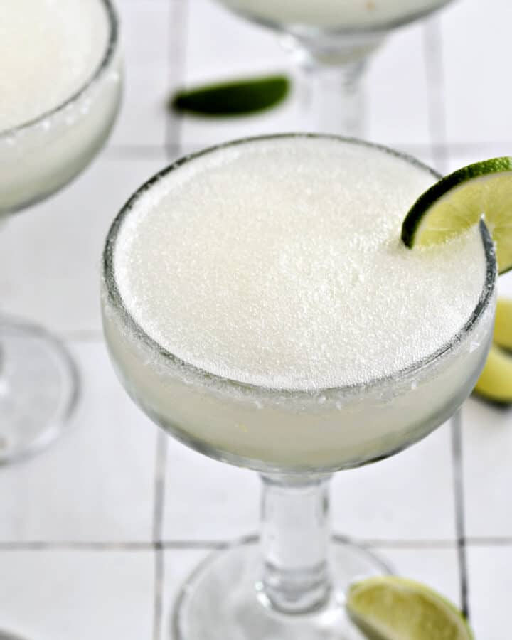 A frozen blended margarita garnished with a lime wheel in a thick margarita glass.
