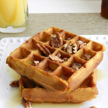 Light and fluffy Pumpkin Waffles topped with maple syrup and toasted pecans! cookingwithcurls.com