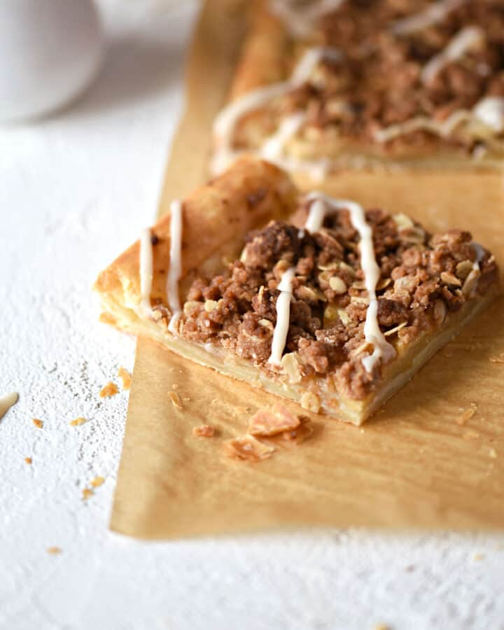 an apple streusel pizza on a sheet of parchment paper with a piece pulled out at an angle with a pitcher of glaze in the background.