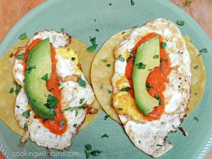 Soft tortilla Huevos Rancheros with pureed sauce and avocado slices on a green plate