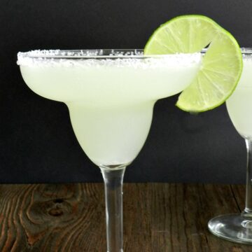 margarita in a glass with salted rim and lime slice