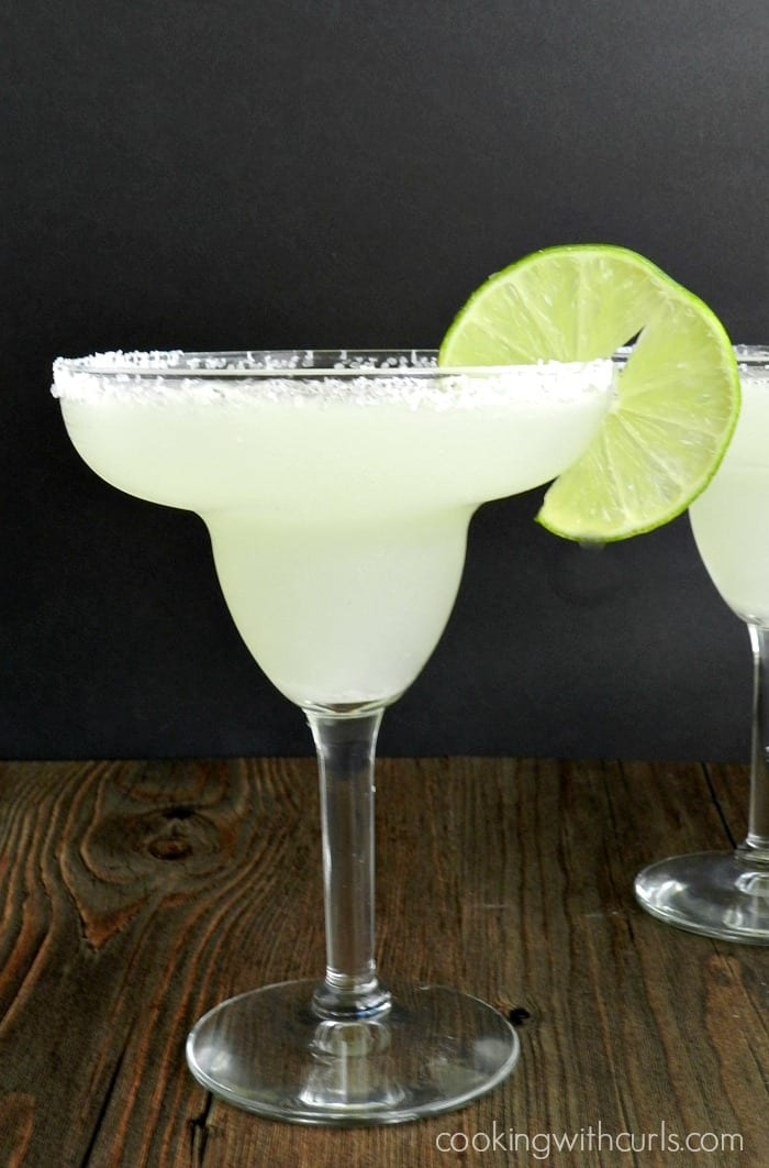 frozen margaritas in salt rimmed margarita glasses with a slice of lime