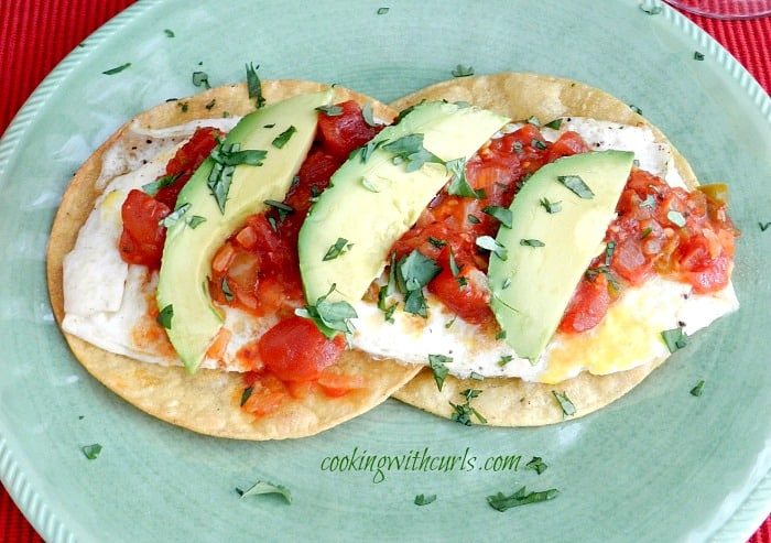 traditional huevos rancheros on a green plate sprinkled with chopped cilantro