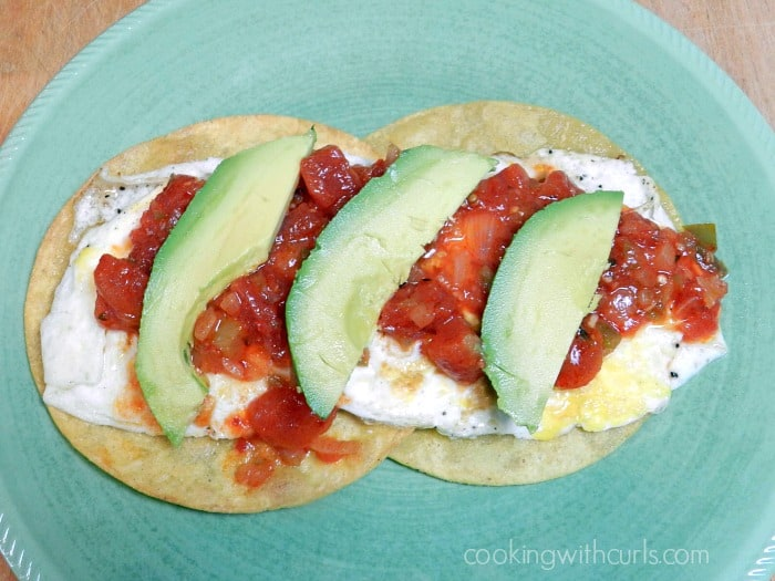 Traditional Huevos Rancheros with chunky sauce and avocado slices on a green plate