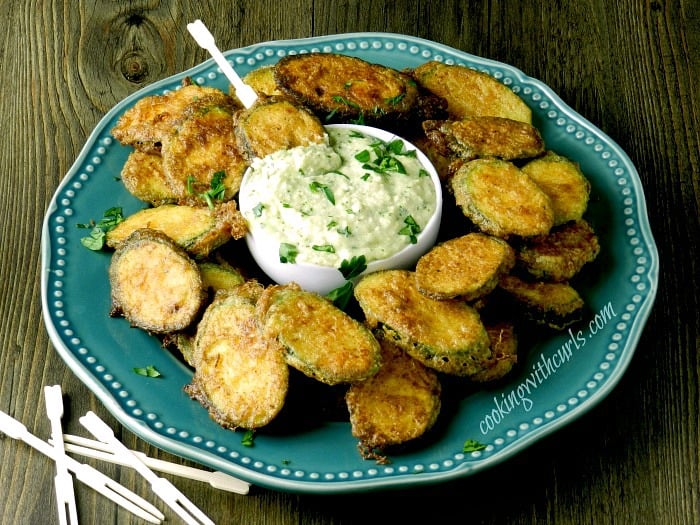 a large blue plate with zucchini fritters surrounding a small white bowl of pine nut sauce