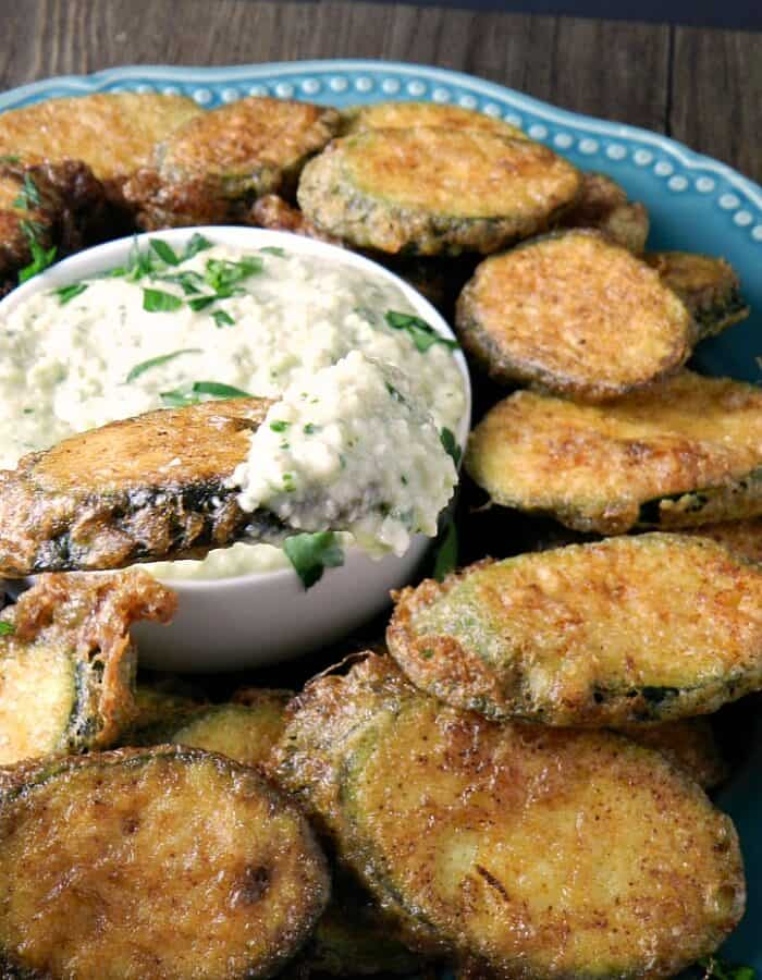 zucchini fritters on a blue plate with pine nut sauce for dipping in a small white bowl in the center