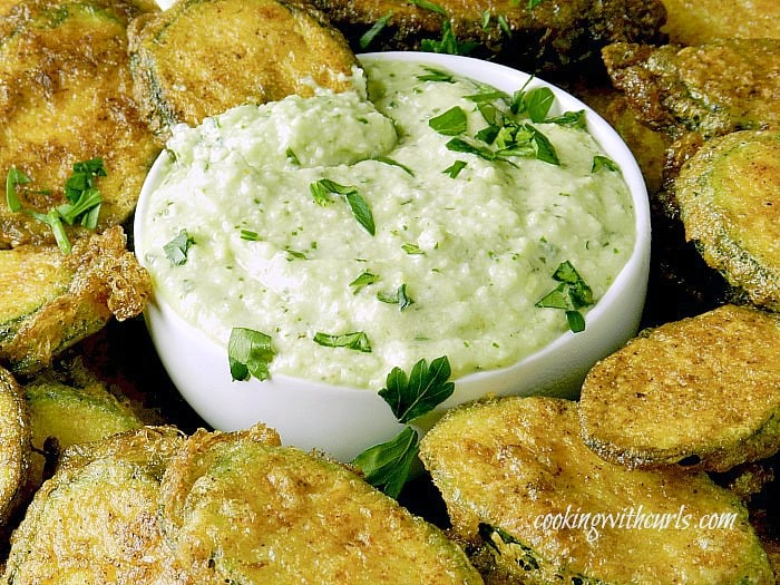 pine nut dipping sauce in a small white bowl surrounded by zucchini fritters