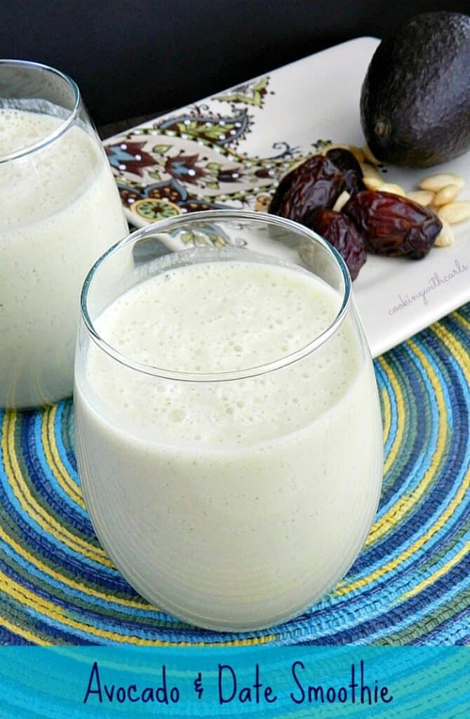 Avocado and Date Smoothie in a small glass sitting on a blue and green spiral placemat, with a plate of dates, avocado and almonds in the background