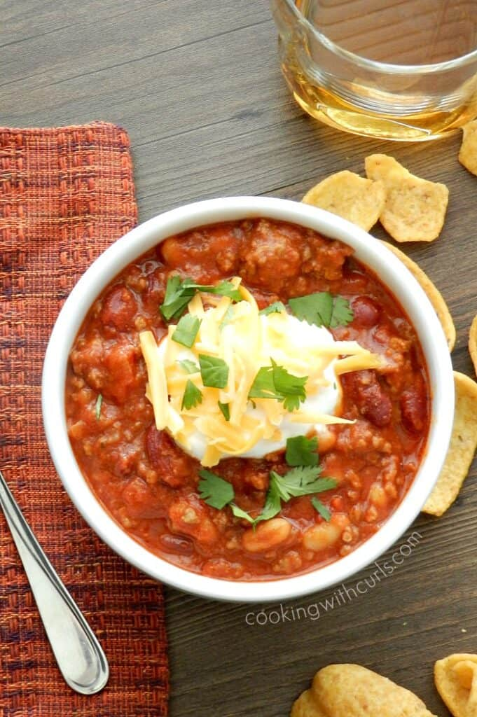 chili in a white bowl with corn chips scattered on the table and a glass of whiskey in the corner