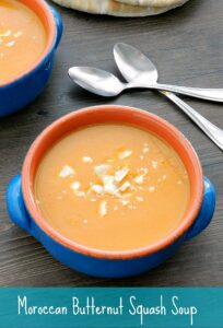 two blue bowls filled with Moroccan Butternut Squash Soup with spoons in the background