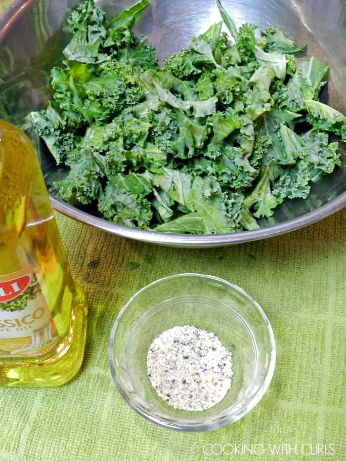 Raw kale in a mixing bowl with oil and seasonings on the side