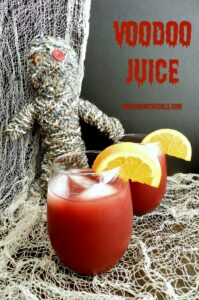 Two glasses of Voodoo Juice sitting in front of a voodoo doll and surrounded by netting