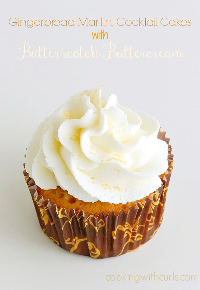 a cupcake wrapped in a brown wrapper with gold leaves and topped with white frosting and gold glitter