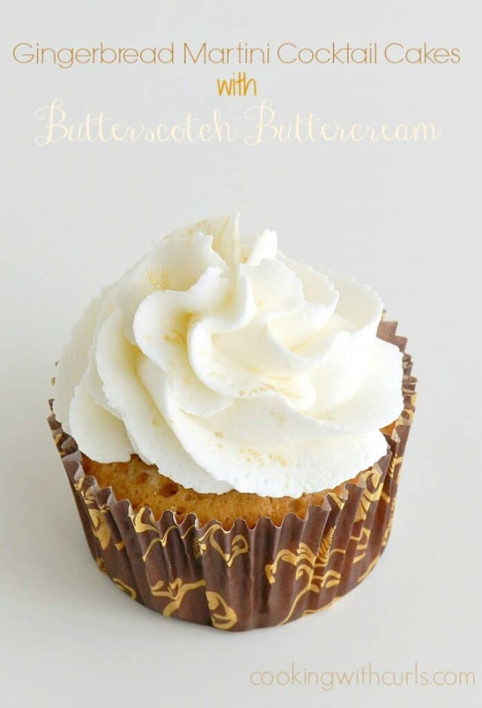 cupcake topped with white frosting and gold glitter wrapped in a brown and gold scroll patterned wrapper