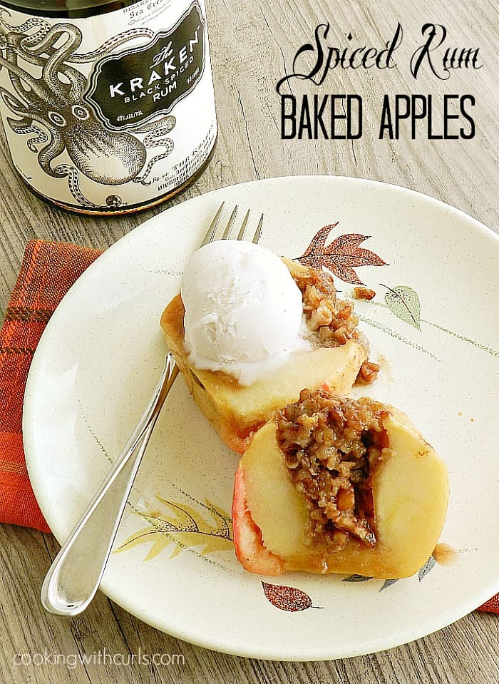 Spiced Rum Baked Apple cut in half and topped with a scoop of vanilla ice cream sitting next to a fork laying on a leaf patterned plate.