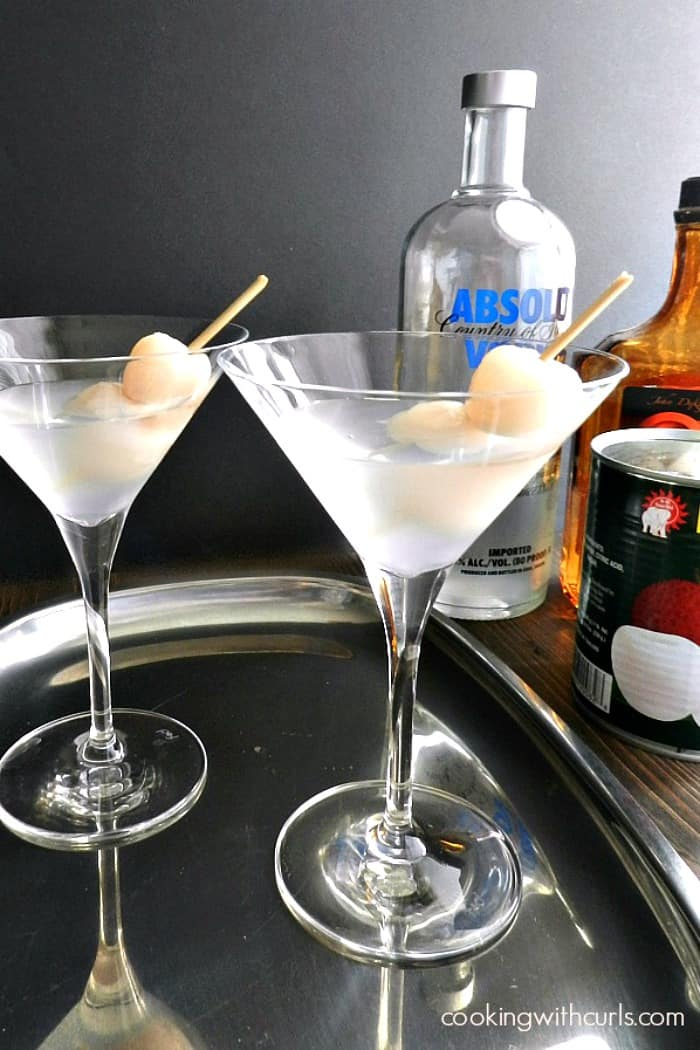 two martini glasses on a silver tray filled with lychee martini and lychees on a toothpick