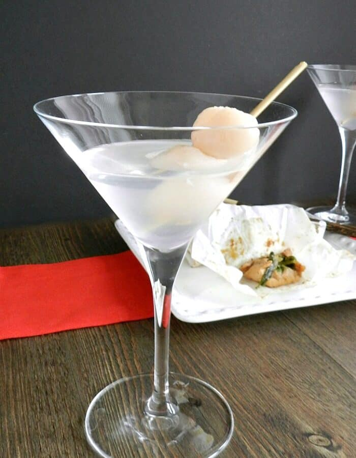 martini glass filled with a lychee martini and a toothpick inserted into two lychees