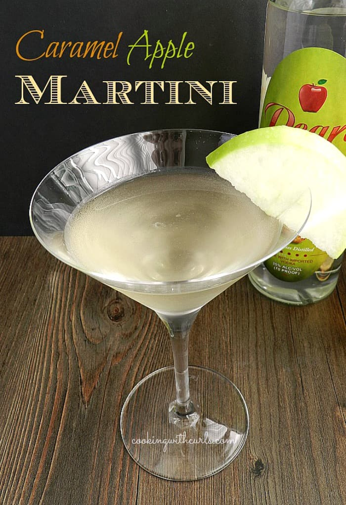 martini glass filled with a cocktail and garnished with a green apple slice sitting in front of a vodka bottle