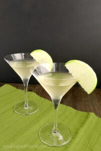 two martini glasses on a green napkin filled with caramel apple martinis and garnished with green apple slices