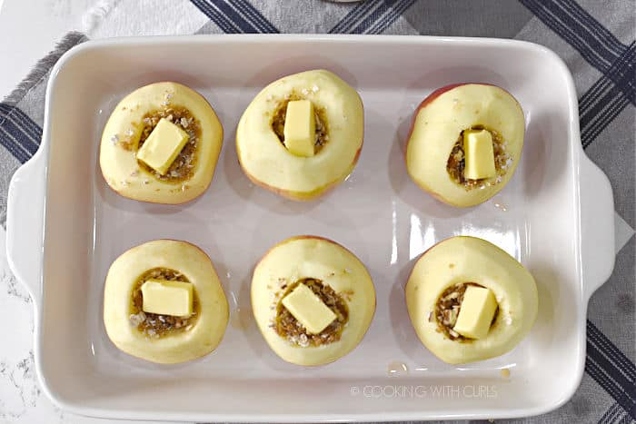 six stuffed apples topped with butter in a white baking dish.